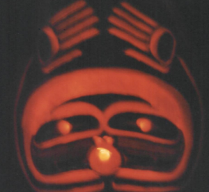 A glowing orange face in the Northwest Coastal Native American art style on a dark background. Candlelight glows from the face's small, circluar mouth, while a pair of long, thin arms with large hands rise above the creature's head.